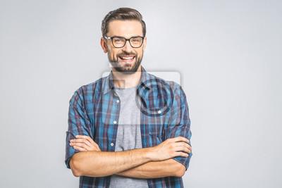 Obraz Szczęśliwy młody człowiek. Portret przystojny młody człowiek utrzymuje ręki krzyżować i ono uśmiecha się w przypadkowej koszula podczas gdy stojący przeciw popielatemu tłu