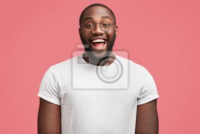 Obraz Talia w górę portret cieszy się ciemnoskórych przystojny mężczyzna model z radosnym wyrazem, nosi okrągłe okulary, będąc w dobrym nastroju jako premii od otrzymania za rzetelną pracę, samodzielnie na