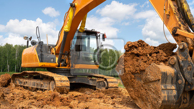 Obraz The excavator works in the field against the background of the forest.