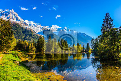 The lake reflects the forest and the blue sky