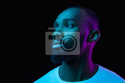Obraz The retro wave or synth wave portrait of a young happy serious african man at studio. High Fashion male model in colorful bright neon lights posing on black background. Art design concept