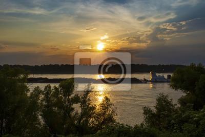 Towboat z barkami w rzece mississippi przy zmierzchem blisko miasta Vicksburg w stanie Mississippi, usa.