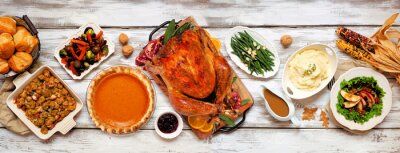 Obraz Traditional Thanksgiving turkey dinner. Above view table scene on a rustic white wood banner background. Turkey, mashed potatoes, stuffing, pumpkin pie and sides.