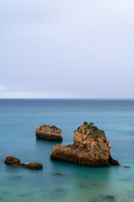 Tranquil scene of the rocks in the acean at the beautiful Ponta Joao de Arens in Portimao, Algarve, Portugal
