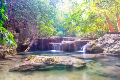 Tropical landscape with beautiful cascades of waterfall and green trees in wild jungle forest. Erawan National park, Kanchanaburi, Thailand