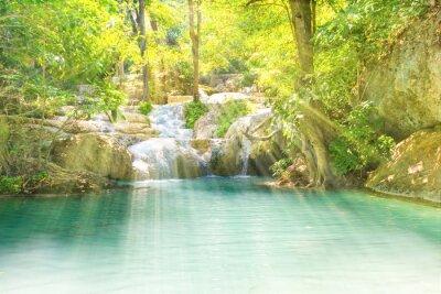 Tropical landscape with beautiful waterfall and emerald lake in green wild jungle forest. Erawan National park, Kanchanaburi, Thailand