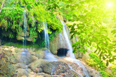 Tropical landscape with beautiful waterfall and rocks in wild green jungle forest. Erawan National park, Kanchanaburi, Thailand
