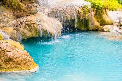 Tropical landscape with beautiful waterfall, emerald blue lake and rocks in wild jungle forest. Erawan National park, Kanchanaburi, Thailand
