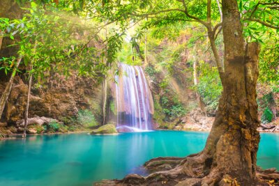 Tropical landscape with beautiful waterfall, emerald lake and green tree in wild jungle sunny forest. Erawan National park, Kanchanaburi, Thailand