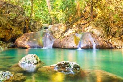 Tropical landscape with beautiful waterfall, emerald lake and rocks in wild jungle forest. Erawan National park, Kanchanaburi, Thailand