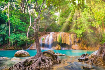 Tropical landscape with beautiful waterfall, emerald lake, rocks and large tree roots in wild jungle forest. Erawan National park, Kanchanaburi, Thailand