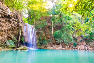 Tropical landscape with beautiful waterfall, wild rainforest with green foliage and flowing water. Erawan National park, Kanchanaburi, Thailand