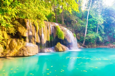 Tropical landscape with beautiful waterfall, wild rainforest with green foliage and flowing water. Erawan National park, Thailand