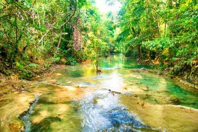 Tropical rainforest landscape with flowing stream and sunrays. Erawan National park, Kanchanaburi, Thailand