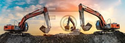 Obraz Trzy koparki pracują na budowie o zachodzie słońca, widok panoramiczny