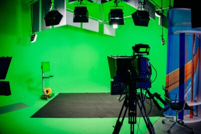 Obraz TV Studio recording show.Reportage shooting.TV NEWS program studio with video camera lens and lights.Positioned stage big professional broadcasting camera with headphones.Green key studio