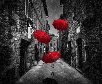 Obraz Umrbellas latające z wiatrem i deszczem na ciemnej ulicy w starym włoskim miasteczku w Toskanii we Włoszech