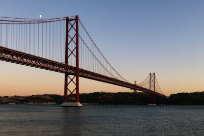 View of the 25 of April Bridge (Ponte 25 de Abril) over the Tagus River, in the city of Lisbon, Portugal; Concept for travel in Portugal