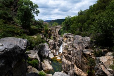 View of the ancient Mizarela Bridge (or Devil's Bridge) with a waterfall, at the Peneda Geres National Park, in Portugal, Europe