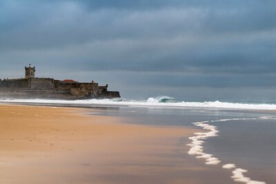 View of the Carcavelos beach in a winter morning with theSao Juliao da Barra Fort with its reflection on the background, and the waves brealing at Carcavelos, Oeiras, Portugal