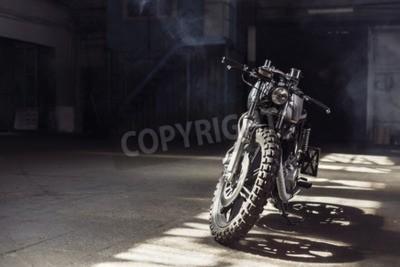 Obraz Vintage motocykl stoi w ciemnym budynku w promieniach światła słonecznego. Stonowane kolory. Przedni widok