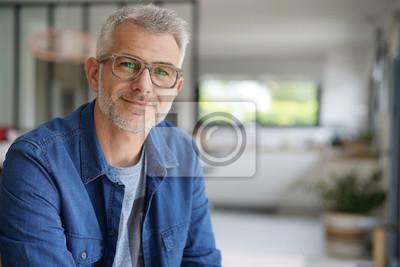 Obraz W średnim wieku facet z okularami i niebieską koszulę