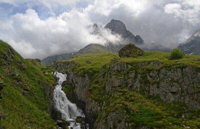 Waterfall among green rocks