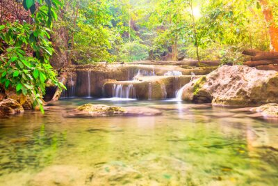 Waterfall landscape with beautiful cascades and green trees in wild jungle forest. Erawan National park, Thailand