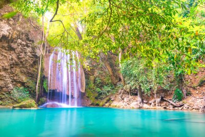 Waterfall landscape with beautiful emerald lake and green tree in wild jungle forest. Erawan National park, Thailand