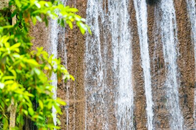 White foam streams of waterfall flowing down from cascade in green tropical jungle forest. Erawan National park, Thailand