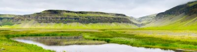 wide angle panorama to little lake and hills in grass in Iceland in summer day