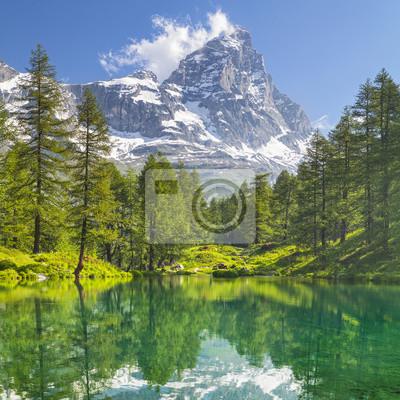 widok na szczyt Matterhorn i jezioro leśne z szmaragdową wodą i sosnami we Włoszech