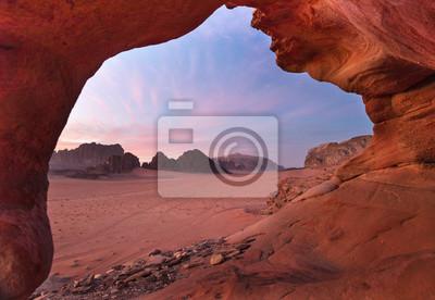 widok przez czerwony kamienny łuk do pięknego zmierzchu na pustyni Wadi Rum w Jordanii
