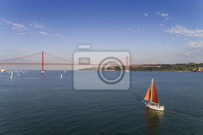Widok z lotu ptaka piękna żagiel łódź na Tagus rzece z 25 Kwietnia most na tle, w mieście Lisbon, Portugalia