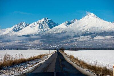 Obraz Winter Driving - Zima Droga Droga krajowa prowadząca przez zimowy krajobraz górski.