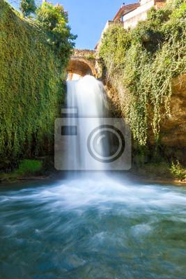 Wodospad przepływa między zielonymi liśćmi. Molinar rzeka płynie przez miasto Tobera tworzących piękne wodospady w prowincji Burgos, Hiszpania