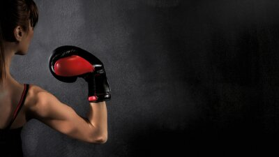 Obraz  Woman Boxer Biceps with Red Boxing Glove on Black Background, high contrast with saturated grunge filter