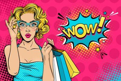 Obraz Wow twarz kobiety. Sexy zaskoczony młoda kobieta w okularach z otwartymi ustami i blond włosy kręcone włosy gospodarstwa torby na zakupy i Wow! pęcherzyk mowy. Wektor jasne tło w pop-art retro komiczn