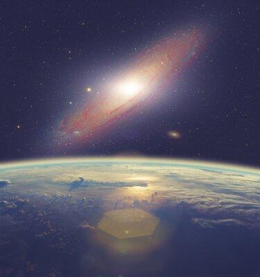 Obraz Wschód słońca nad Ziemi z wielką Galaktyka Andromedy.