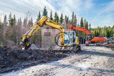 Obraz Yellow and orange excavator building a road deep in the forest. Rusko, Finland.