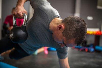 Obraz Young man podnoszenia hantle i kettlebell w centrum fitness