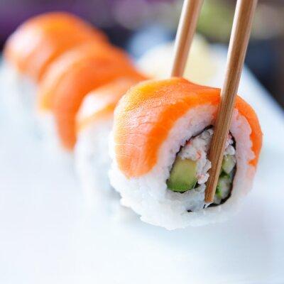 Obraz zbierając kawałek sushi pałeczkami