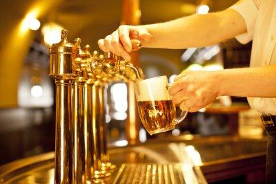 Obraz złoty piwo w dłoni i piwo kranów