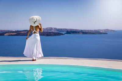 Plakat A beautiful woman in a white summer dress stands by the pool and enjoys the breathtaking view over the mediterranean sea