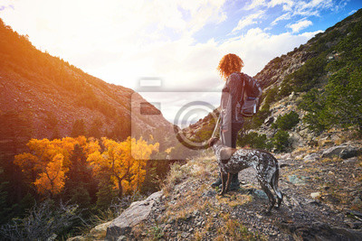 Plakat a young woman and her dog hiking to the top of a mountain