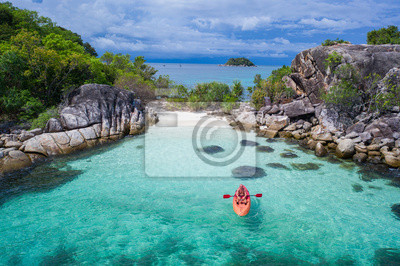 Plakat Aerial drone view of man kayaking in crystal clear lagoon sea water during summer day near Koh Kra island in Thailand. Travel tropical island holiday concept