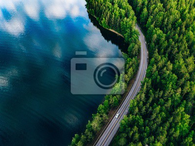 Plakat Aerial view of road between green forest and blue lake in Finland