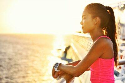Plakat Aktywna kobieta relaks po pracy na statku patrząc na morze w czasie letnich wakacji. Asian girl lekkoatleta noszenia SmartWatch tętna Activity Monitor zdrowego stylu życia.