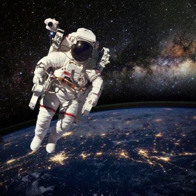 Plakat Astronauta w przestrzeni kosmicznej nad ziemią w porze nocnej. Elem