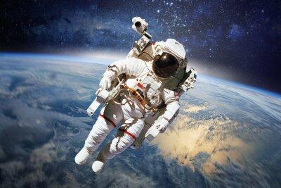 Plakat Astronauta w przestrzeni kosmicznej z planety Ziemia w tle. Elementy